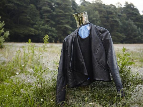 Eine Lederjacke hängt an einem Ast in der Natur