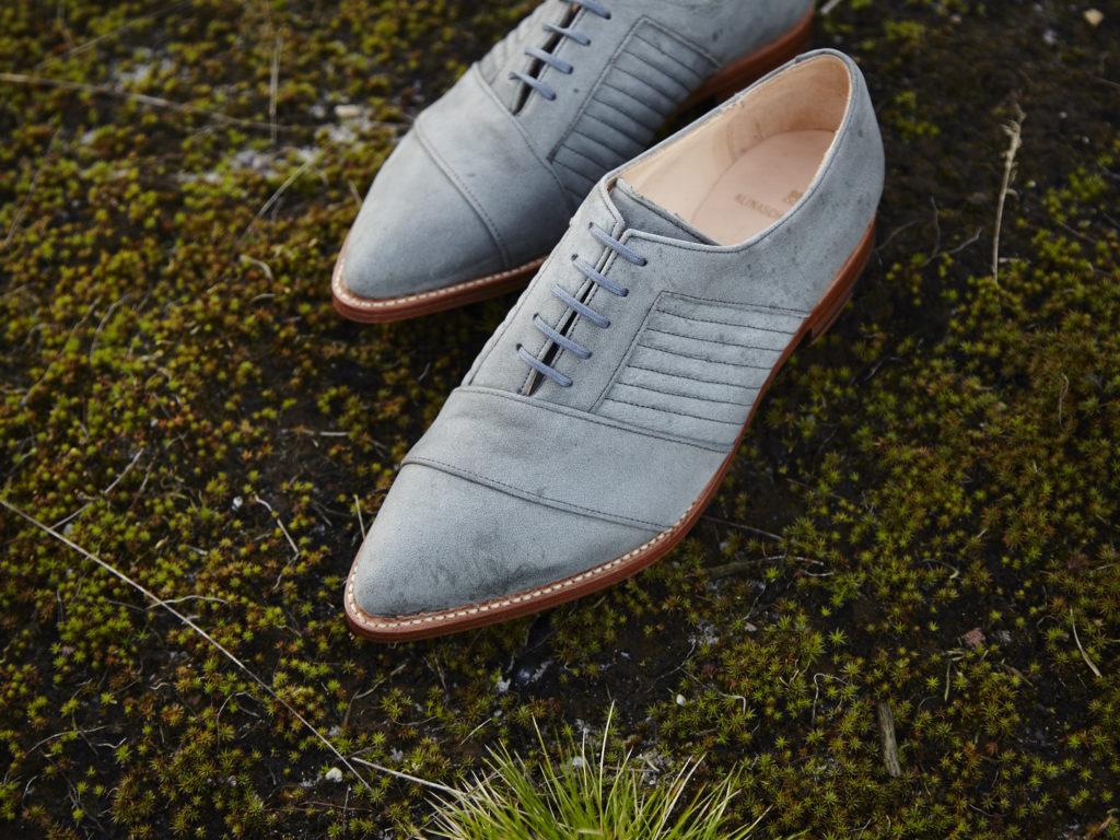 Hellblaue vegane Schuhe stehen auf der Erde