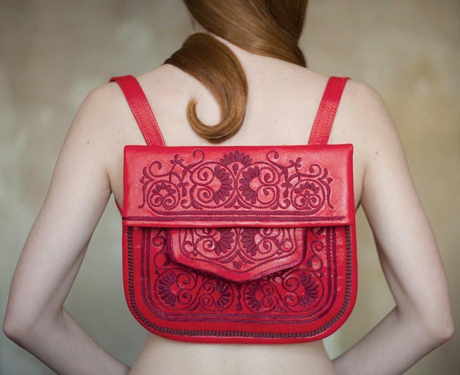 Ein Model trägt einen roten Rucksack von dem Label Abury
