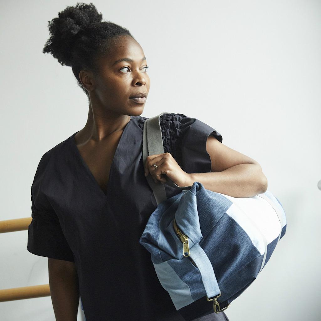 Eine Frau trägt eine blaue Patchwork-Tasche