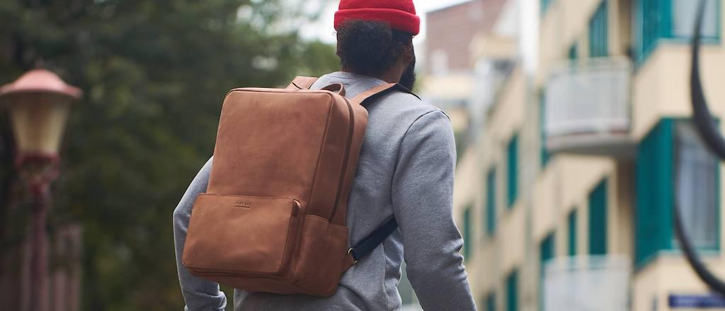 Ein Mann trägt einen braunen Rucksack