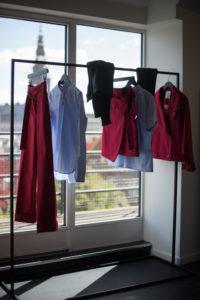 Blaue und rote Kleidung hängt an einer Kleiderstange