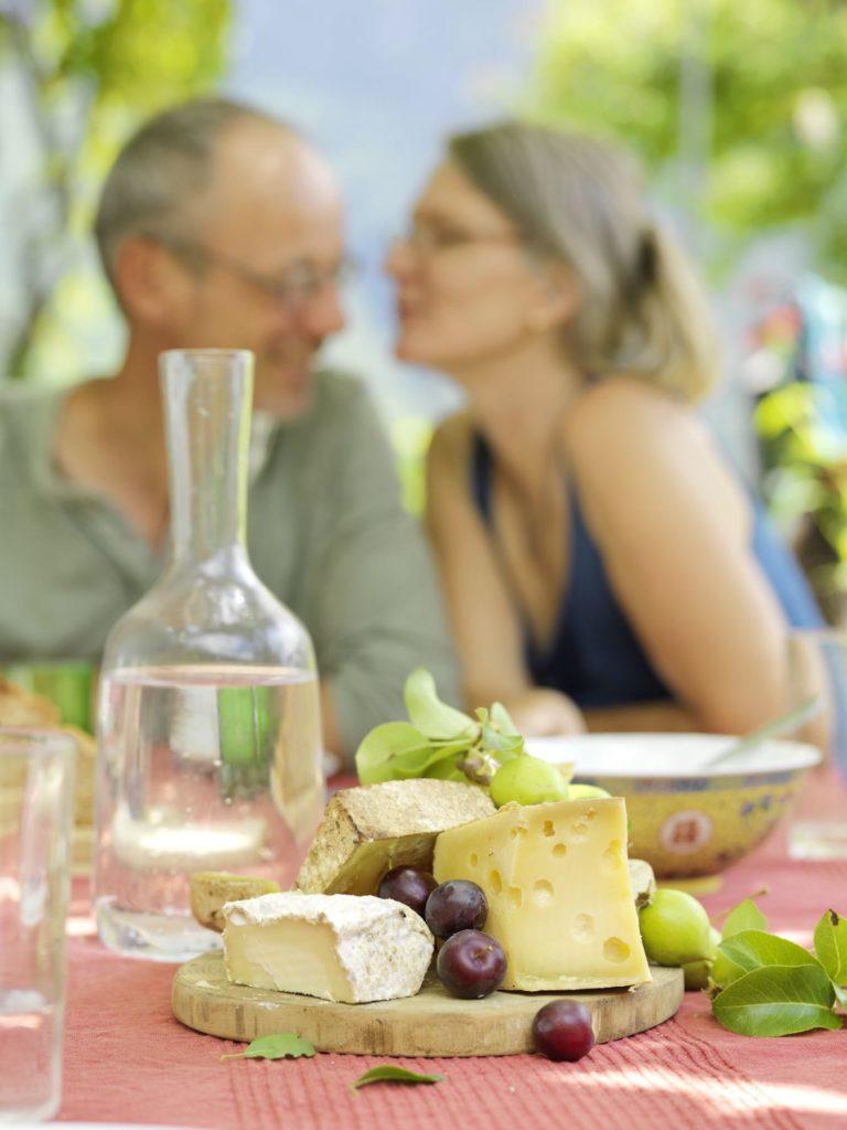 Ein Mann und eine Frau vor einem Käsebrett