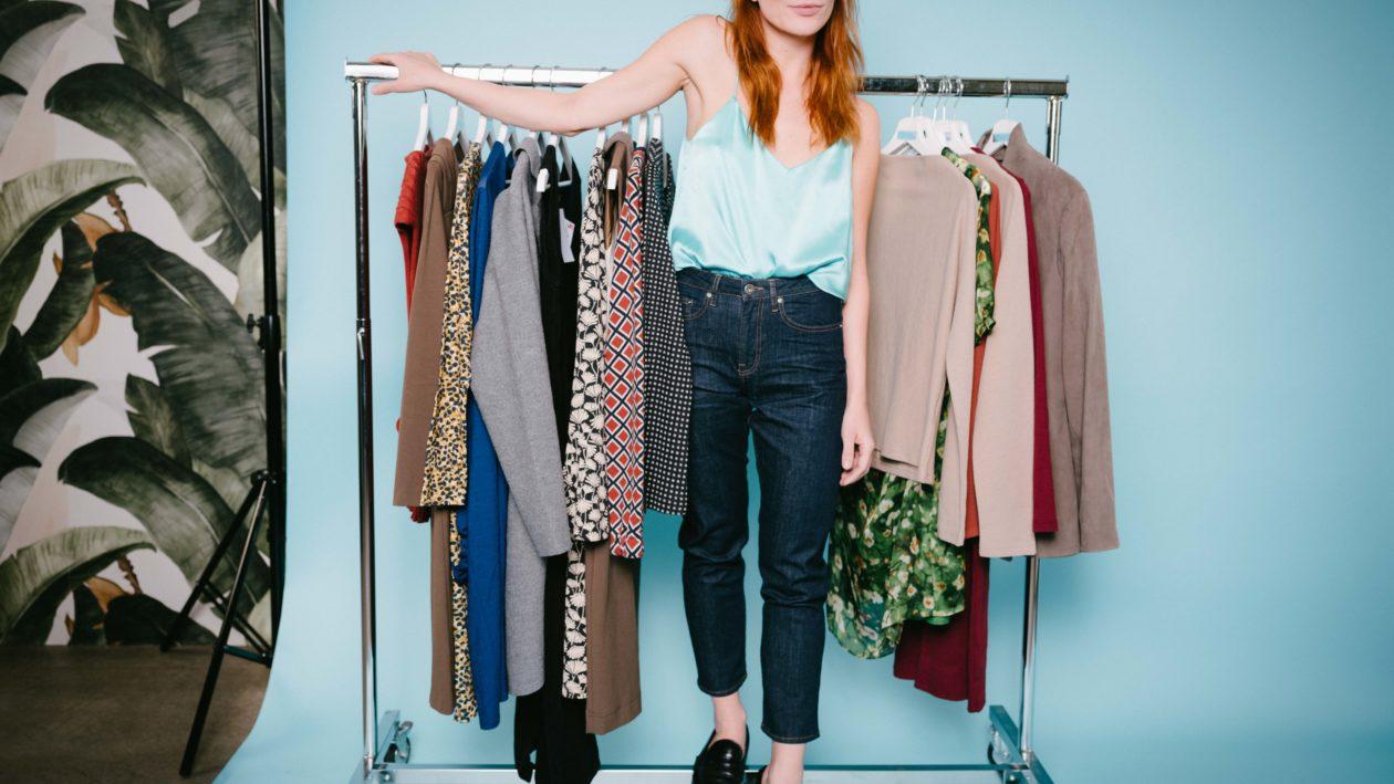 Eine Frau steht neben einer Kleiderstange