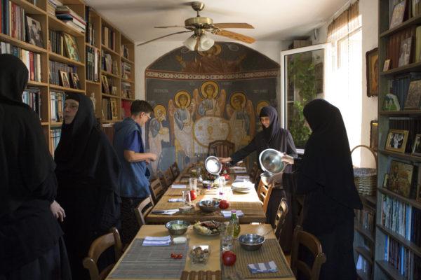 Mittagessen wird abgeräumt. Nonnen unterhalten sich.