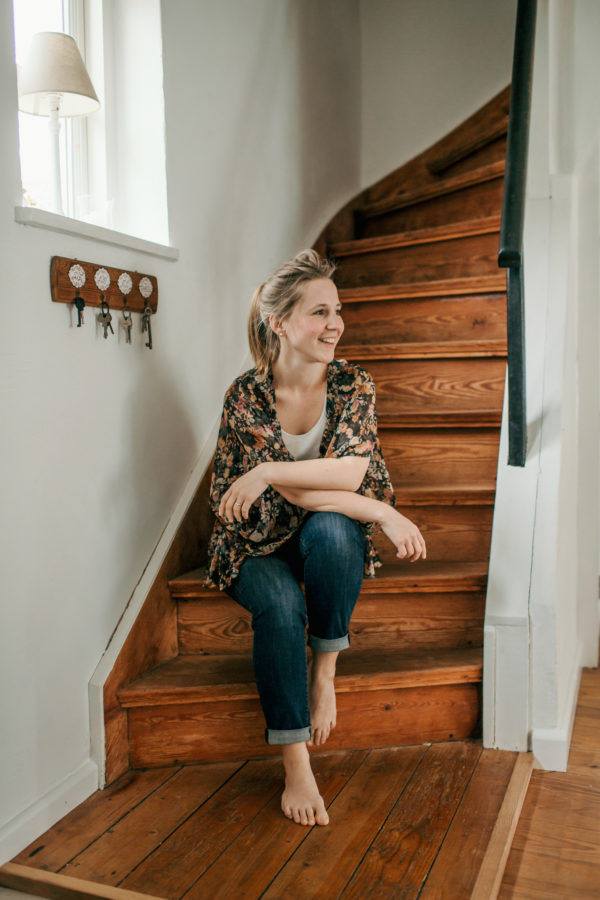 Eine blonde Frau sitzt auf einer Holztreppe