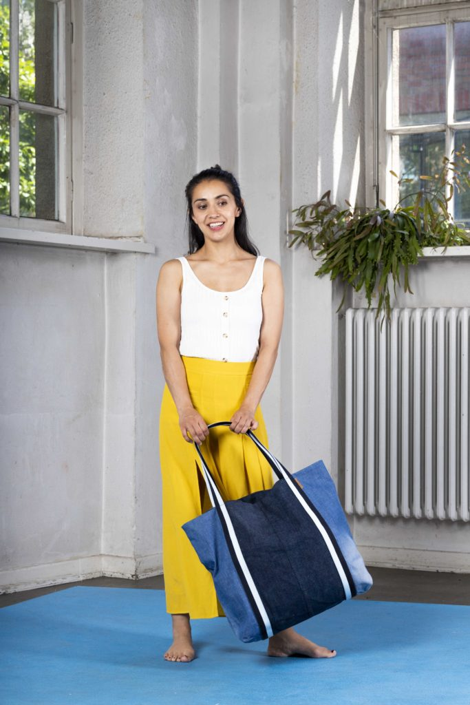 Ein Model trägt eine gelbe Hose und eine große Tasche