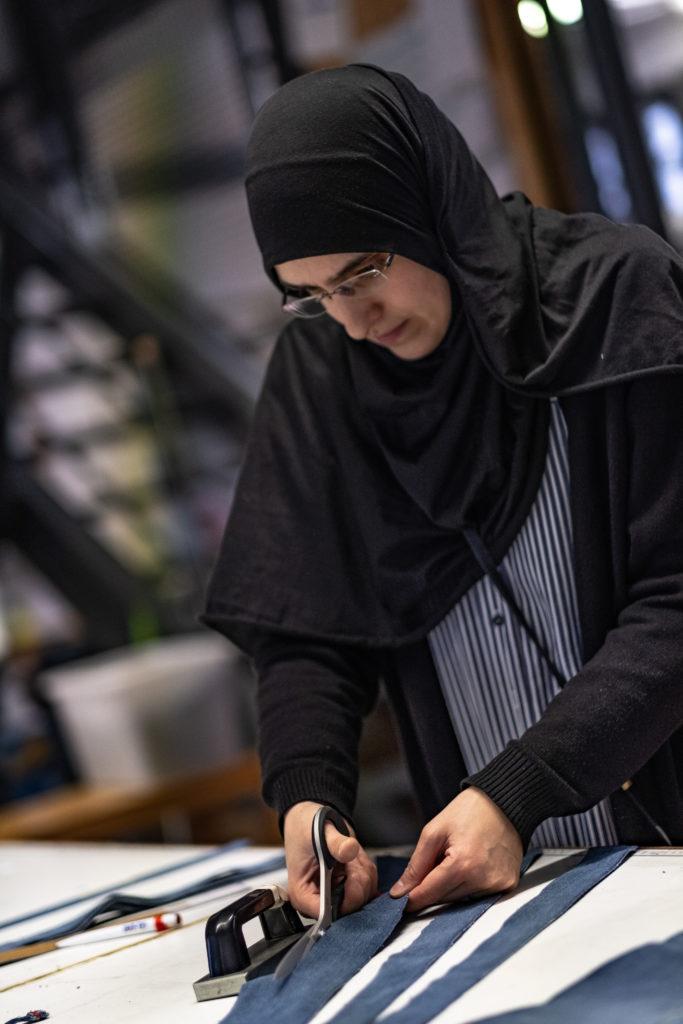Eine Frau mit Kopftuch schneidet einen Stoff zu