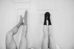 Zwei paar Beine mit Socken an den Füßen lehnen an der Wand