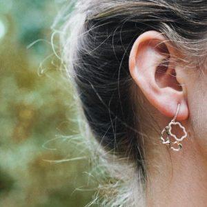 Eine blonde Frau mit einem goldenen Ohrring von Vieri Fine Jewellery