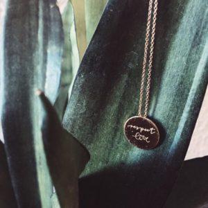 Eine goldene Halskette von Vieri Fine Jewellery hängt vor einem Pflanzenblatt