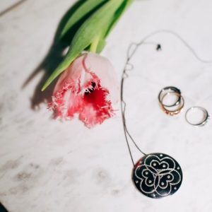 Eine Kette und drei Ringe von Vieri Fine Jewellery liegen neben einer pinken Blume auf dem Tisch