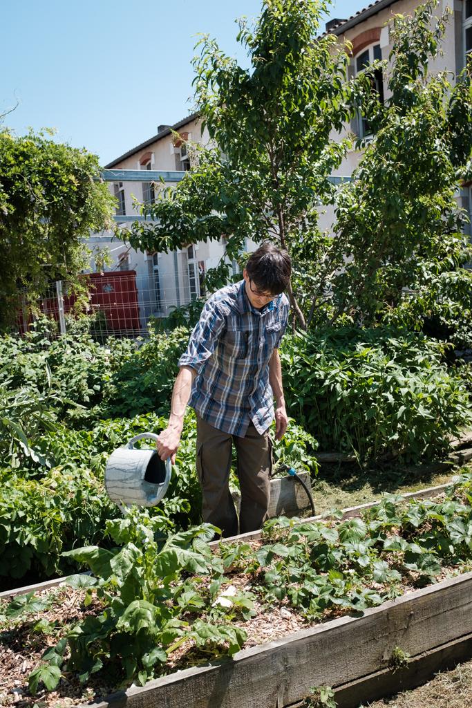 Ein Mann in Albi gießt seinen grünen Garten