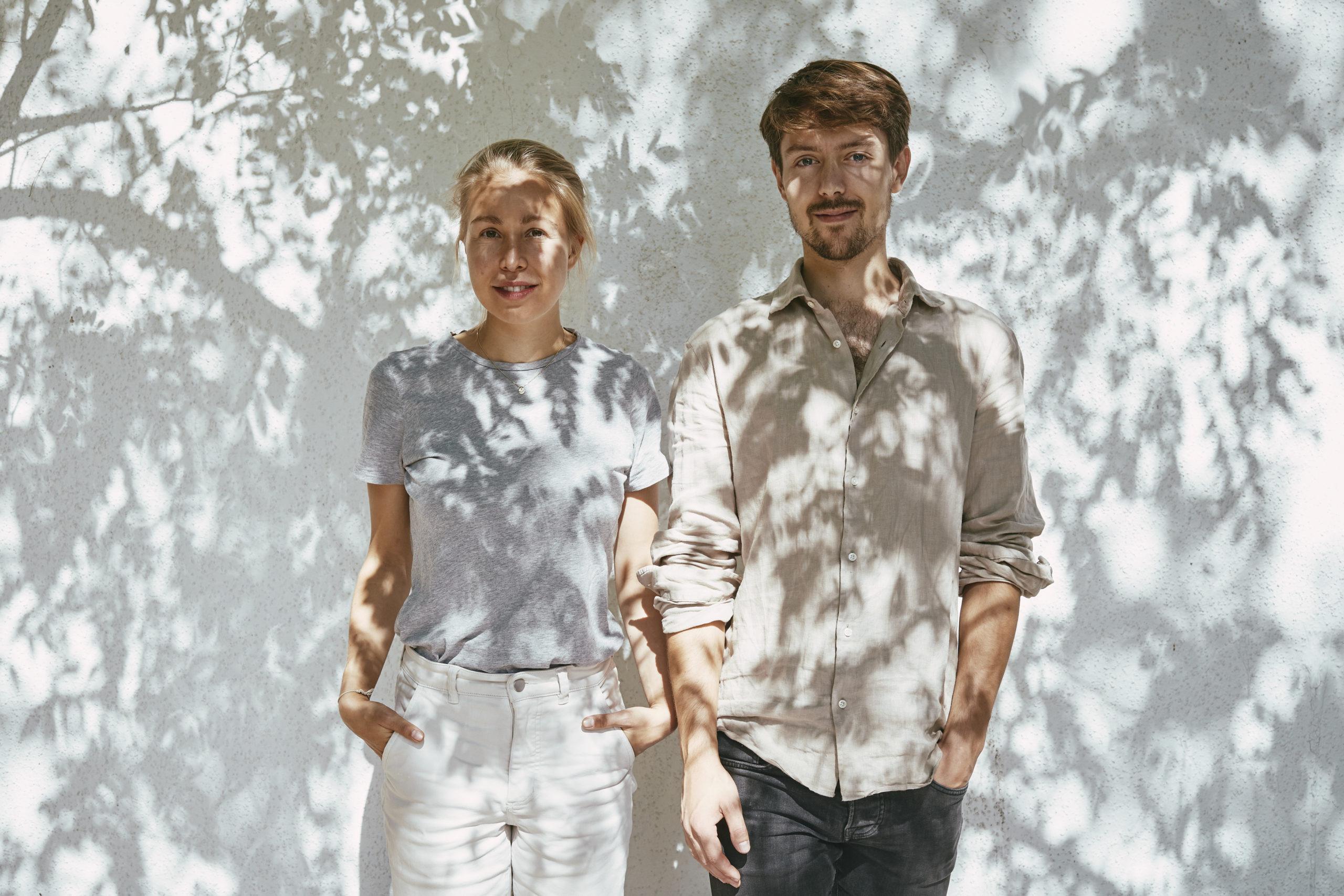 Die beiden Gründer von dem Start-Up Kruut stehen vor einer weißen schattigen Wand