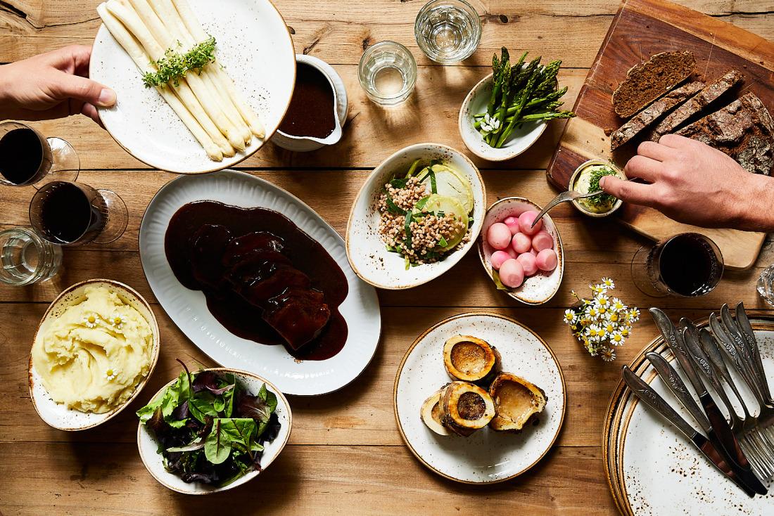 Zwei Leute nehmen sich von einem gedeckten Tisch mit mehreren Gerichten