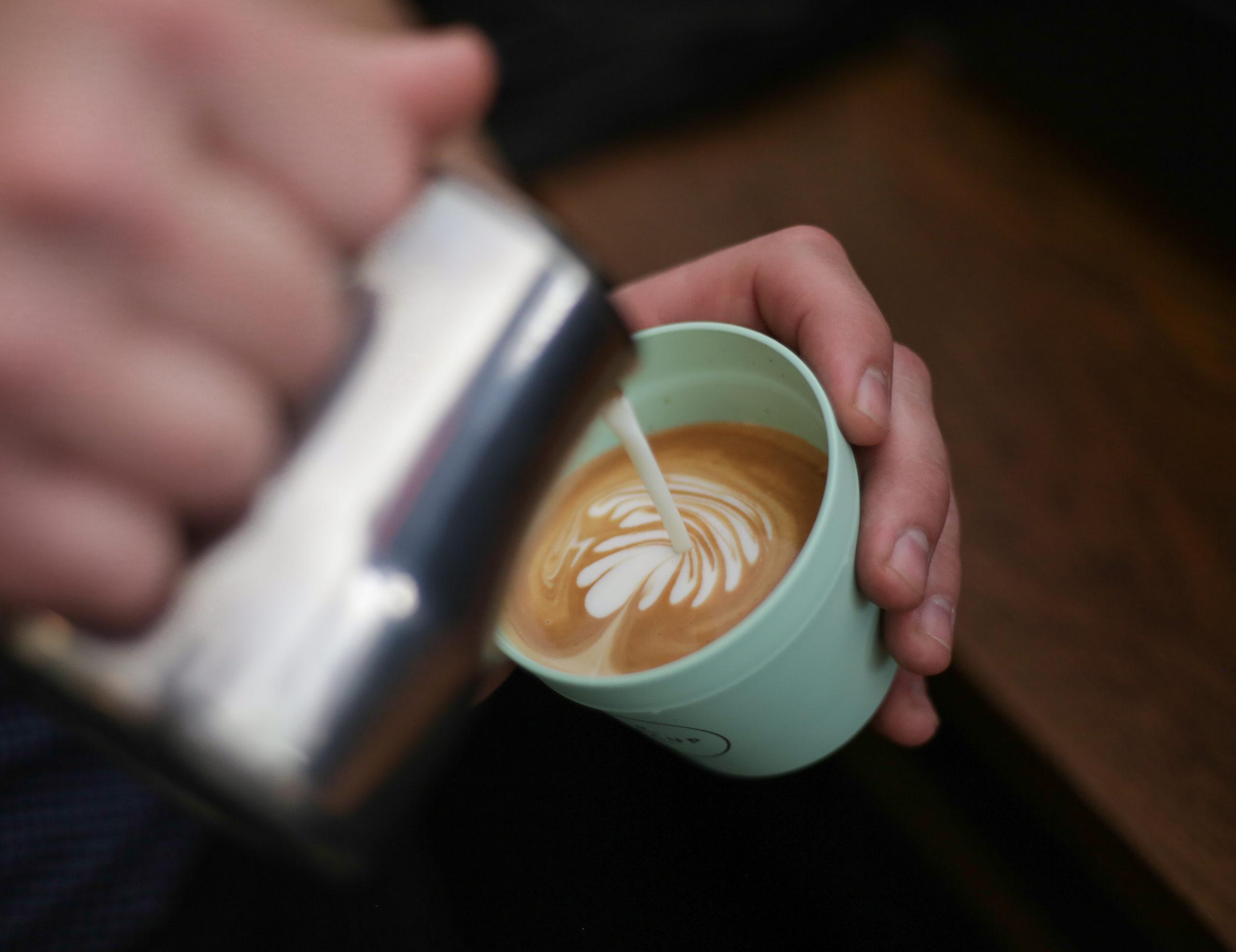 Ein Barista schenkt Kaffee in einen Recup-Becher